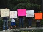 Jovenes Oaxaqueños Sostienen pancartas en apoyo a Oaxaca